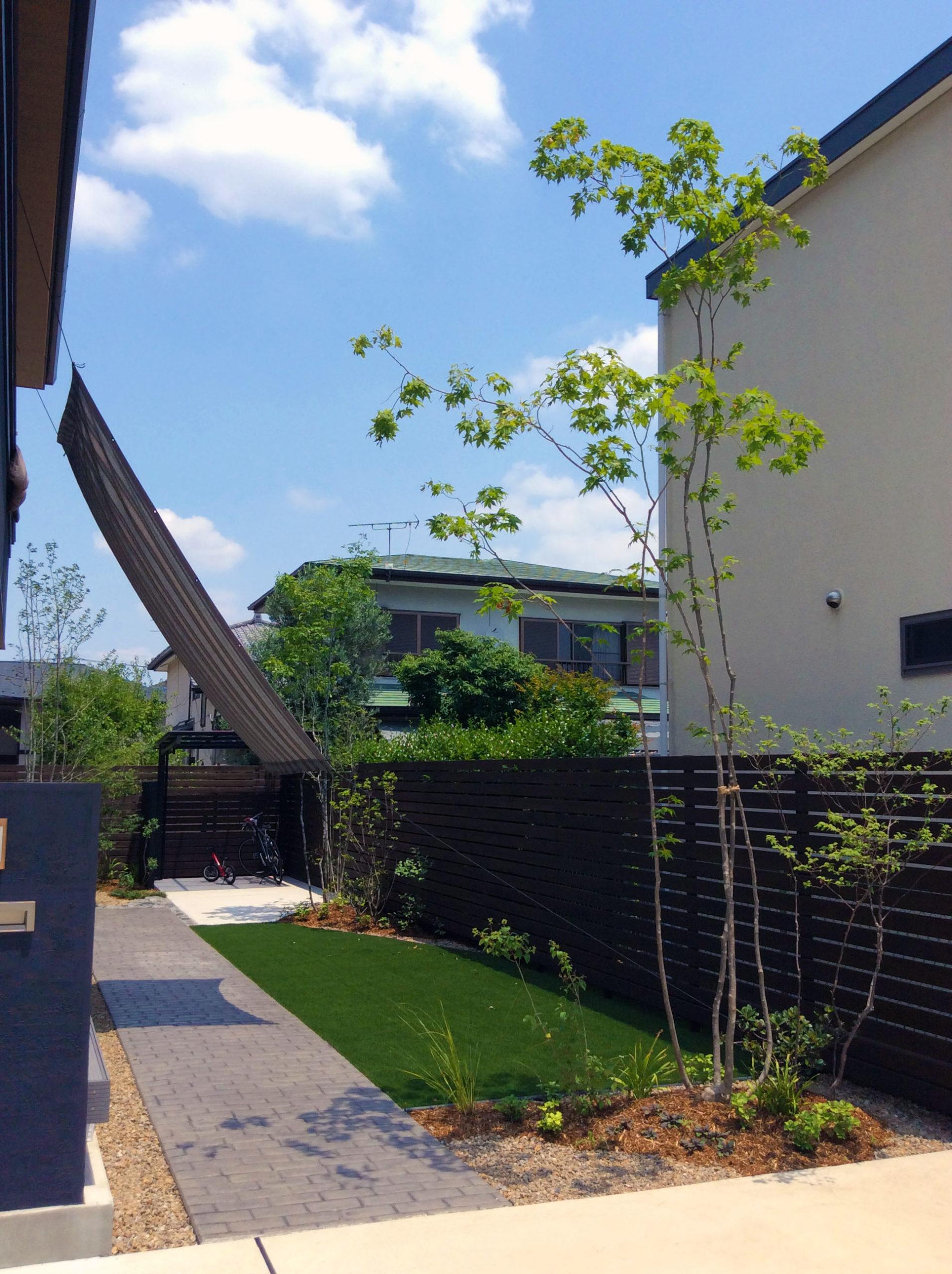 生きた樹木が美しい人工芝のローメンテナンスガーデン
