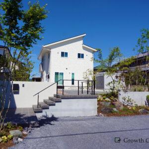 高低差のある土地に建てられた白い家。家から道路までの外構工事は、お庭にも駐車場にも子供の遊び場にもなる多目的な空間に。さわやかな庭木と自然造形を再現した外構デザインがおしゃれです。